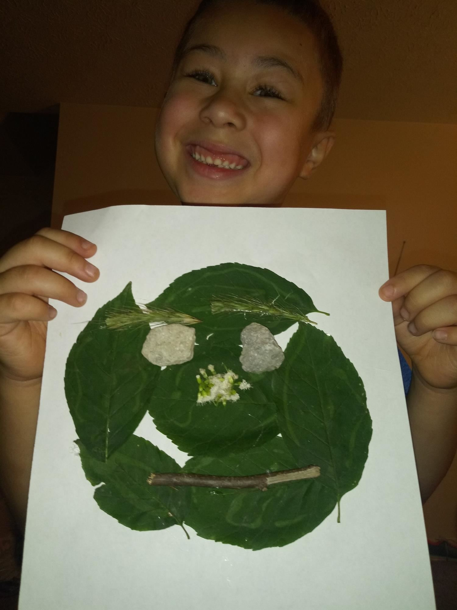 Kindergartener Montez Jones shows off her nature face created using leaves, twigs, and rocks